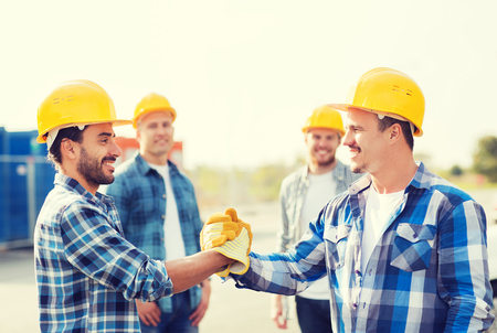 personas saludandose: business, building, teamwork, gesture and people concept - group of smiling builders in hardhats greeting each other with handshake outdoors