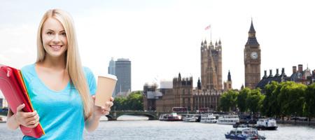 onderwijs, school, studie in het buitenland, drankjes en mensen concept - lachende student meisje met mappen en kopje koffie in london stad achtergrond Stockfoto