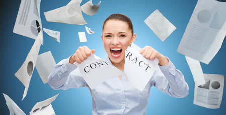 tearing: business, emotion, fail and people and concept - angry businesswoman tearing contract over blue background Stock Photo
