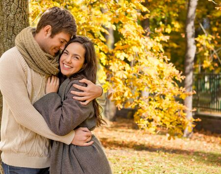natural love: love, relationship, family, season and people concept - smiling couple hugging over autumn natural background