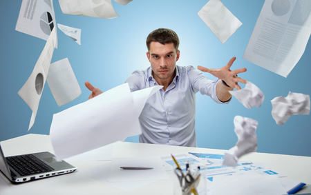 work stress: business, people, stress, emotions and fail concept - angry businessman throwing papers in office over blue background