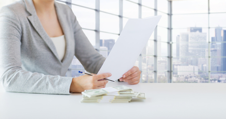 finance report: business, finance, tax and people concept - close up of woman hands with us dollar money and tax report paper form over city office room background