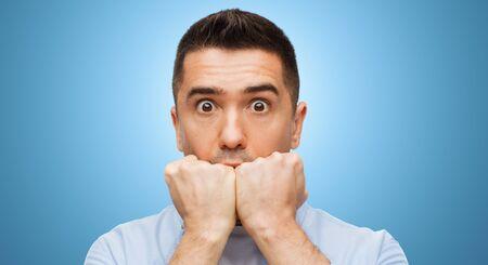 공포, 공포, 감정 및 사람들이 개념 - 파란색 배경 위에 무서 워 남자 얼굴