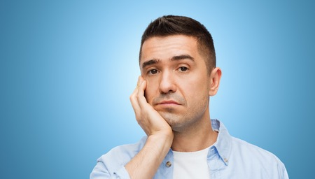 man looking: emotions and people concept - bored middle aged man face over blue background