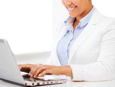 african business: business and technology concept - african businesswoman with laptop in office