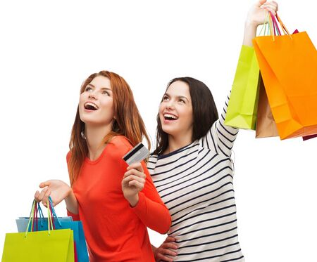 purchases: shopping, sale and gifts concept - two smiling teenage girls with shopping bags and credit card