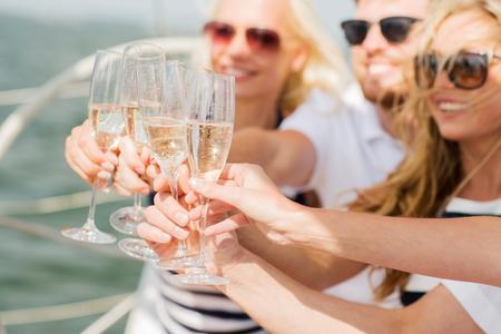 Urlaub, Reisen, Meer, Urlaub und Menschen Konzept - Nahaufnahme von glückliche Freunde Gläser Champagner und Segeln auf Yacht Klirren Standard-Bild