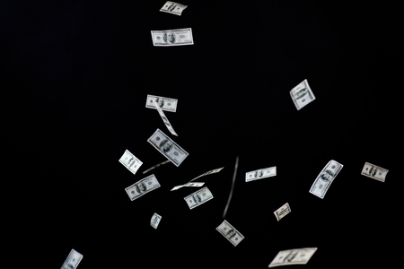 flying money: business, finance, waste and concept - close up of us dollar money flying over black background