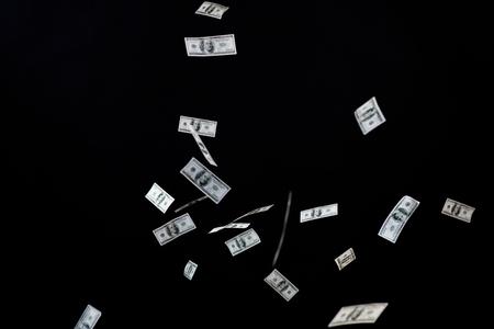 dinero volando: negocios, las finanzas, los residuos y el concepto - cerca de nosotros dinero del dólar volando sobre fondo negro