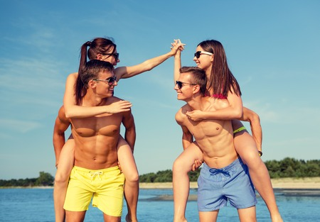 women having fun: friendship, sea, summer vacation, holidays and people concept - group of smiling friends wearing swimwear and sunglasses having fun on beach Stock Photo