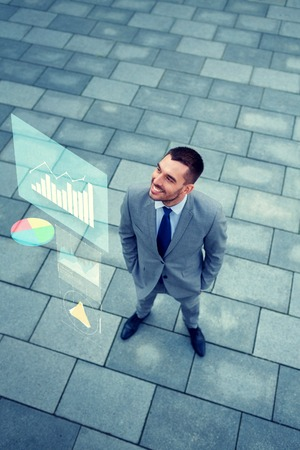 people development: business, development and people concept - young smiling businessman with growth chart outdoors from top