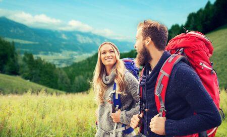 travel woman: adventure, travel, tourism, hike and people concept - smiling couple walking with backpacks over alpine hills background