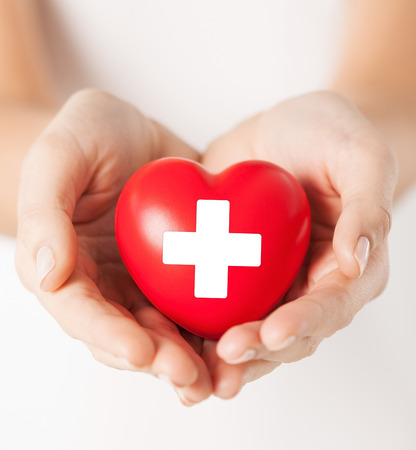 salud de la familia, la caridad y la medicina concepto - las manos femeninas sosteniendo el corazón rojo con el signo de la cruz