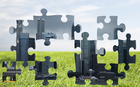 urbanization: nature, urbanization, ecology and environment concept - puzzle with city peaces over blue sky and grass background