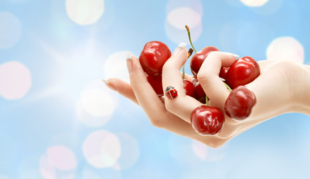 people, summer, fruits hand berries concept - female hand full of red cherries over blue lights background photo