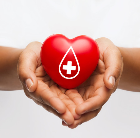 healthcare, medicine and blood donation concept - african american female hands holding red heart with donor sign Stock Photo