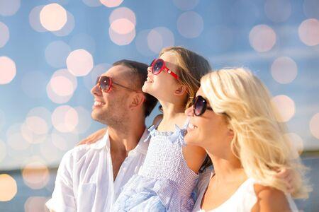 Urlaub Sommer, Konzept Kinder und Menschen - glückliche Familie in den Sonnenbrillen über blauen Lichter Hintergrund Standard-Bild
