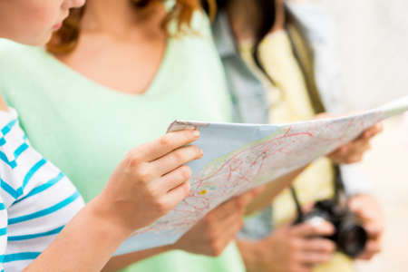 lost city: tourism, travel, leisure, holidays and friendship concept - close up of women with map and camera outdoors