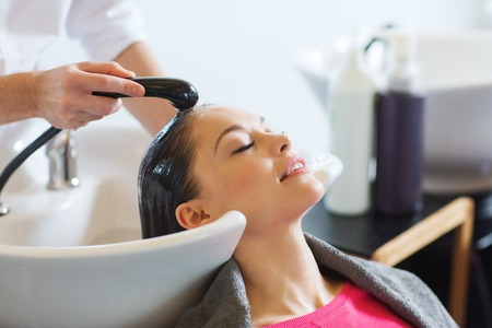 hair and beauty: beauty and people concept - happy young woman with hairdresser washing head at hair salon Stock Photo