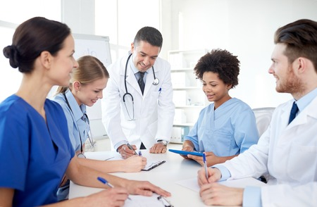 medical education, health care, people and medicine concept - group of happy doctors or interns with mentor meeting and taking notes at hospital