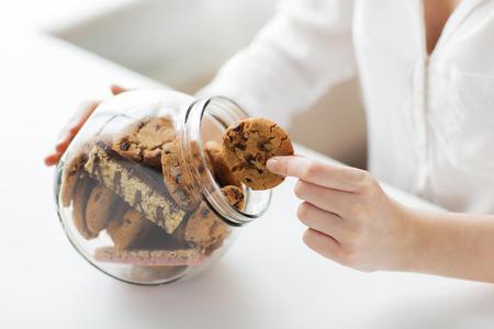 la gente, la comida basura, culinaria, el bicarbonato y el concepto de alimentación poco saludable - cerca de las manos con las galletas de avena de chocolate y barritas de muesli en el tarro de cristal