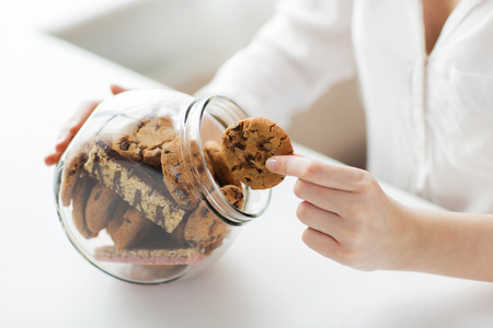 chocolate cookies: people, junk food, culinary, baking and unhealthy eating concept - close up of hands with chocolate oatmeal cookies and muesli bars in glass jar
