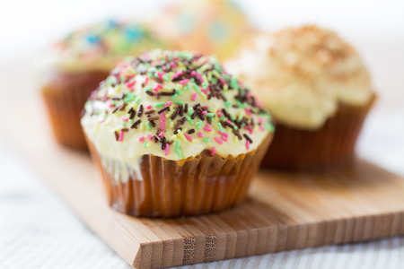 junkfood: food, junk-food, culinary, baking and eating concept - close up of glazed cupcakes or muffins on wooden board