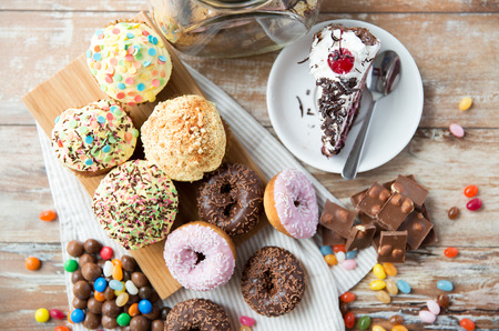 junk food, culinary, baking and eating concept - close up of glazed donuts, cakes and chocolate sweets on table 스톡 콘텐츠
