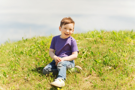 5 6 years: summer, childhood, leisure and people concept - happy little boy sitting on grass outdoors Stock Photo