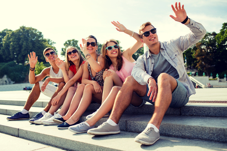 waving: friendship, leisure, summer, gesture and people concept - group of smiling friends sitting on city street and waving hands