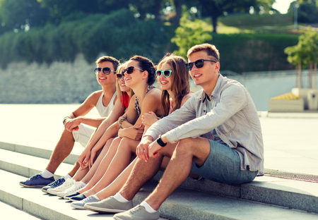youth group: friendship, leisure, summer and people concept - group of smiling friends sitting on city square Stock Photo