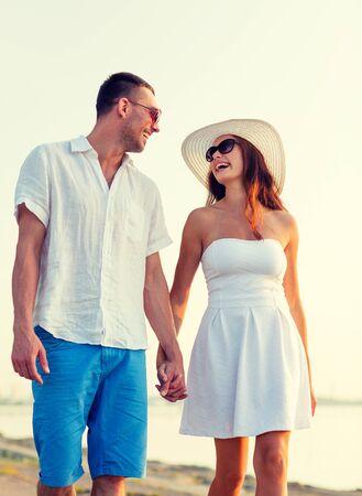 amore, viaggi, turismo, estate e la gente concept - sorridente coppia in vacanza indossando occhiali da sole e si tengono per mano camminando in riva al mare