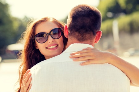 love park: love, wedding, summer, dating and people concept - smiling couple wearing sunglasses hugging in park