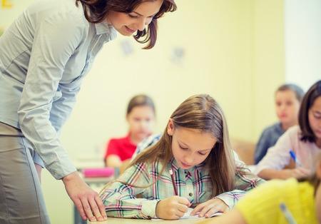 educación, escuela primaria, el aprendizaje y el concepto de la gente - profesor de ayudar a niña de la escuela escribía la prueba en el aula Foto de archivo
