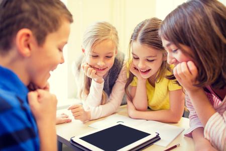 Bildung, Grundschule, Lernen, Technologie und Menschen Konzept - Gruppe von Schulkindern mit Tablette-PC-Computer, die Spaß auf Pause im Klassenzimmer