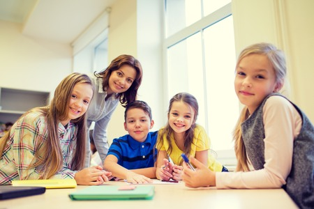 grade school age: education, elementary school, learning and people concept - teacher helping school kids writing test in classroom
