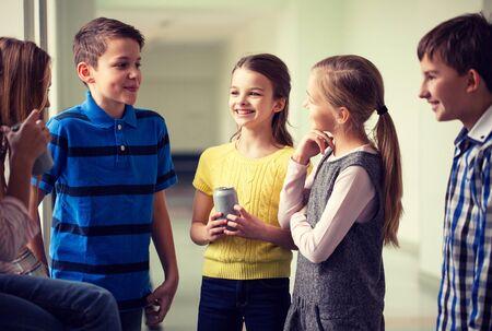 Onderwijs, basisschool, drankjes, kinderen en mensen concept - groep schoolkinderen met frisdrankblikken praten in de gang