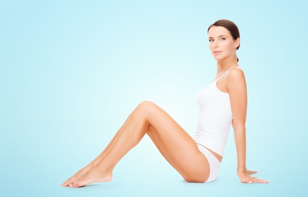 beauty body: people, beauty and body care concept - beautiful woman in cotton underwear showing her legs over blue background Stock Photo