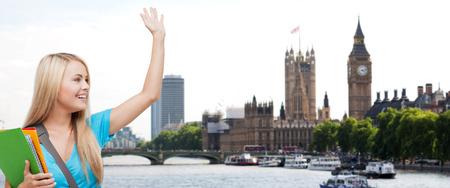 onderwijs, school, studie in het buitenland, gebaar en mensen concept - lachende student met mappen wuivende hand over London City en Thames River achtergrond