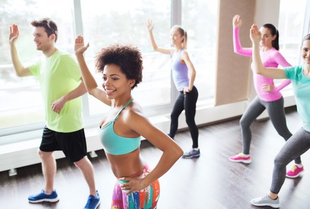 latin dance: fitness, sport, dance and lifestyle concept - group of smiling people with coach dancing zumba in gym or studio