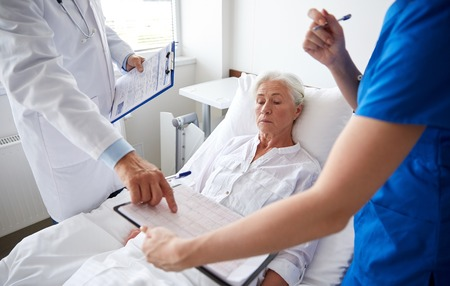 man in hospital bed: medicine, age, health care and people concept - doctor and nurse with clipboards visiting senior patient woman at hospital ward Stock Photo