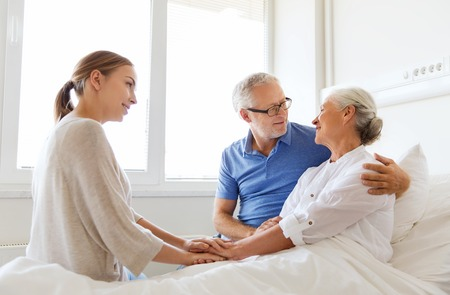 medicine, support, family health care and people concept - happy senior man and young woman visiting and cheering her grandmother lying in bed at hospital ward Reklamní fotografie