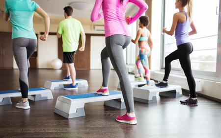 fitness, sport, opleiding, aerobics en mensen concept - close-up van de mensen uit te werken met steppers in de gymzaal van rug