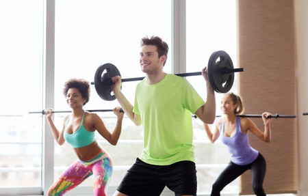barbell: fitness, sport, training, gym and lifestyle concept - group of people exercising with barbell and bars in gym Stock Photo