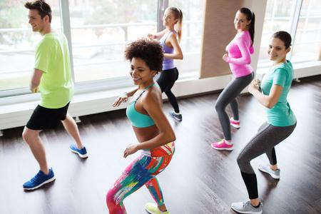 fitness, sport, tanec a koncept životního stylu - skupina lidí, usměvavá se trenér taneční Zumba v tělocvičně nebo studiu