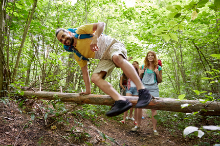 MOCHILA: aventura, viaje, turismo, caminata y concepto de la gente - grupo de amigos sonrientes caminando con mochilas y saltar sobre tronco de un árbol caído en el bosque