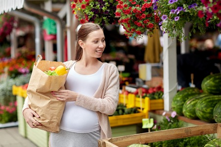 woman eating: sale, shopping, pregnancy and people concept - happy pregnant woman with paper bag full of food at street market