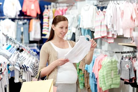 clothing shop: pregnancy, people, sale and expectation concept - happy pregnant woman with shopping bag buying baby bodysuit at children clothing store