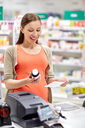 pharmaceutics: pregnancy, medicine, pharmaceutics, health care and people concept - happy pregnant woman with medication and prescription paper at pharmacy cash register