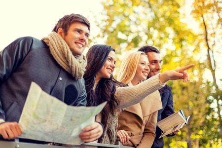 tourists: travel, people, tourism, gesture and friendship concept - group of smiling friends with map standing on bridge and pointing finger in city park
